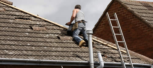 Contractor on tile roof repairing tile